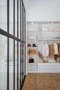 white crisp shelves with very few clothing items displayed. Look to be basic items
