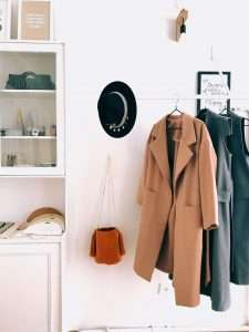 clothing rack with trench coat and dress, hape and purse. Timeless pieces for a capsule wardrobe