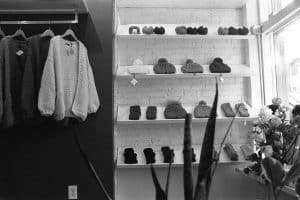 black and white clothes on hangers and folded representing essentials for a capsule wardrobe