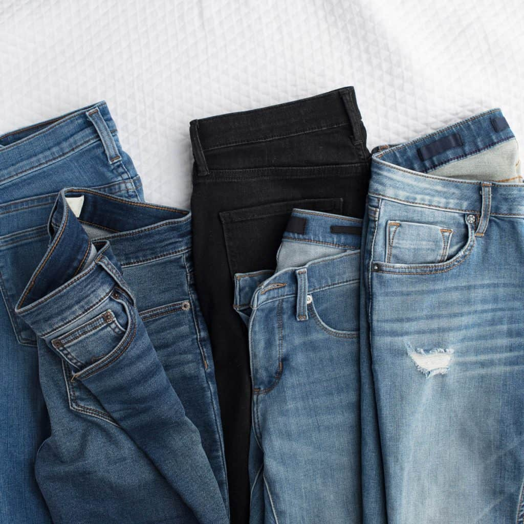 4 pairs of blue jeans folded to show elevated basics