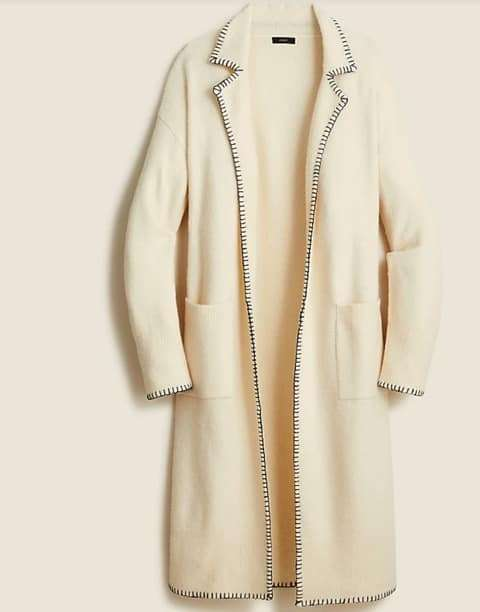 Long off white sweater coat with black stitching on the collar as a timeless wardrobe staple